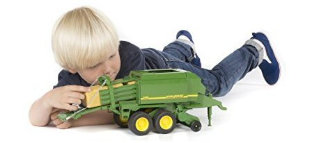 Child playing with a Bruder baler hold on to bale