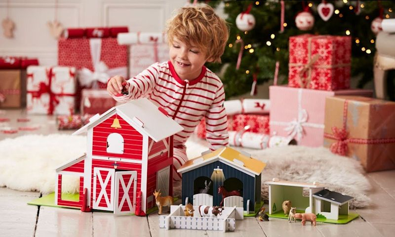 Child playing with ELC wooden farm set